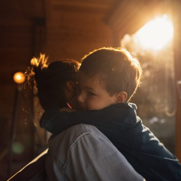 Photo of young mother bonding with her son in a log cabin during winter holidays